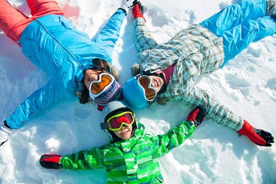 family-of-three-lying-in-snow-fun
